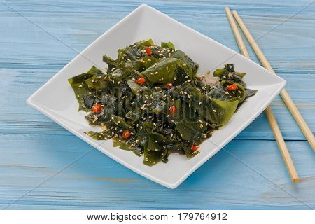 Wakame salad on a small white plate with a pair of chopsticks against a blue background.