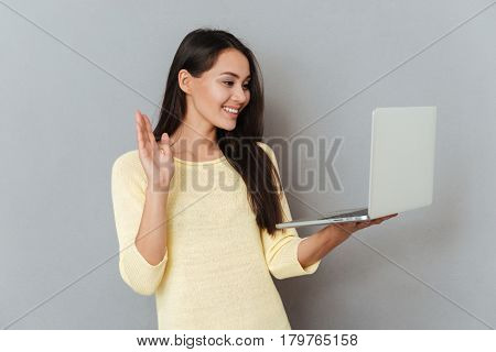 Cheerful charming young woman holding laptop and having video conference over grey background