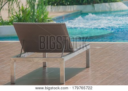Relaxation Concept : Daybed beside swimming pool on wooden floor with blue green water background.