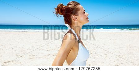 Relaxed Woman In White Swimsuit At Sandy Beach