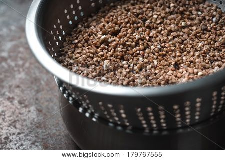 Buckwheat in the metal colander horizontal background, table