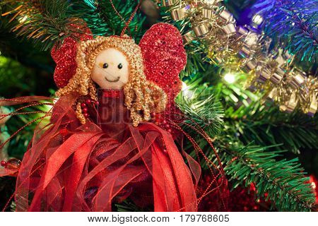 Cute Christmas tree red angel close up on a decorated Christmas tree