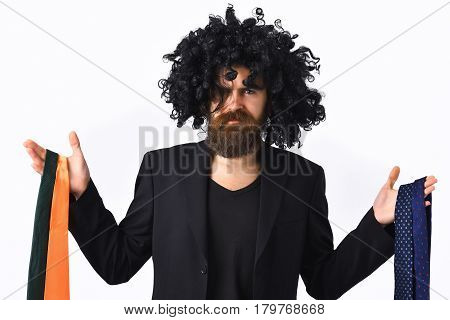 Caucasian Hipster In Suit And Black Curly Wig Holding Ties