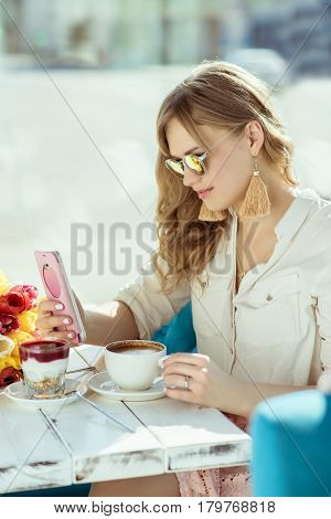 Morning. Girl with the phone cup of coffee and yogurt