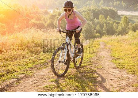 Young girl riding a Bicycle uphill. Background forest