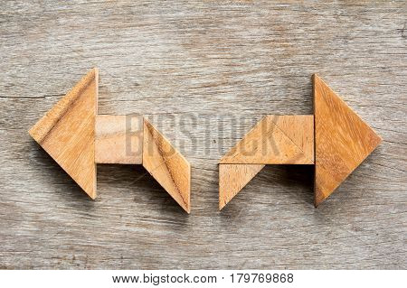 Tangram puzzle as two way arrow shape on wooden background