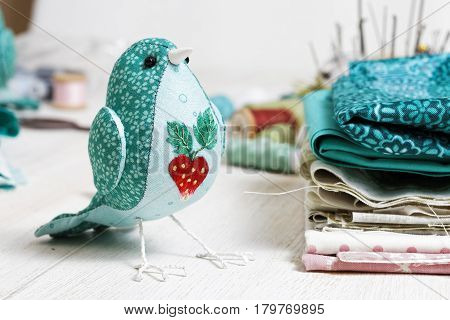 Handmade Bird Sewed From A Cloth Stands On A White Wooden Table Surrounded By Handicraft  Materials.