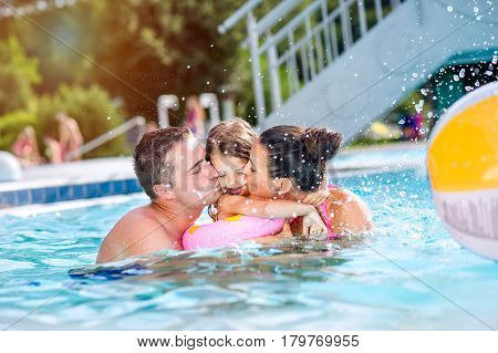 Young mother and father with their daughter in inflatable ring in swimming pool in aqua park, kissing her on cheeks. Summer heat and water.