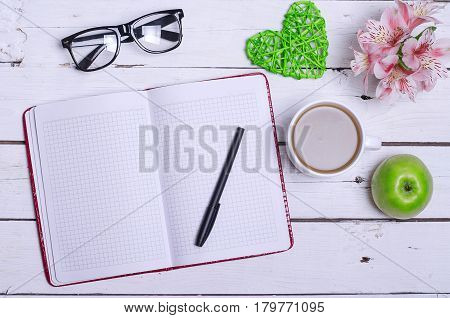 Notepad For Notes, Pen, Glasses And A Cup Of Hot Coffee On A Wooden Table.
