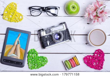A tablet with vacation photos glasses an old camera and a cup of coffee on a wooden table. Lovely breakfast: coffee flowers apple.