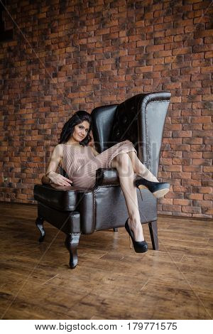 Tall slender brunette next to a black leather armchair in the studio