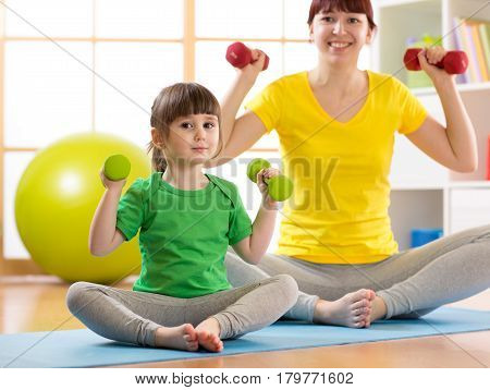 Young woman and her child daughter doing fitness exercises with dumbbells