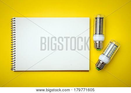 Energy saving LED light bulb with empty notepad on a yellow background