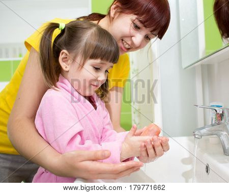 Mother and kid daughter washing their hands in bathroom. Care and concern for children.