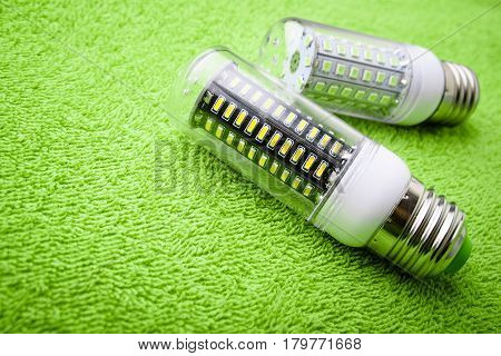 Energy saving LED light bulb on a green background with empty space
