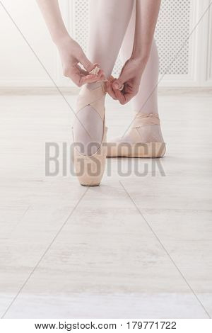 Closeup legs of ballerina who puts on pointe shoes. Ballet practice on training. Beautiful slim graceful feet of dancer, unrecognizable female.