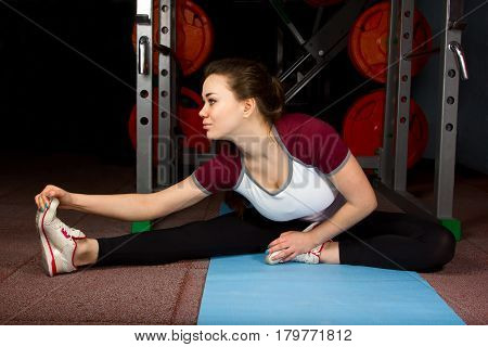 Girl practicing in the gym doing workout stretching