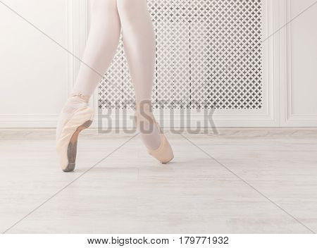 Ballerina legs crop stand on pointe shoes at white wooden floor background, with copy space. Ballet practice. Beautiful slim graceful feet of ballet dancer.