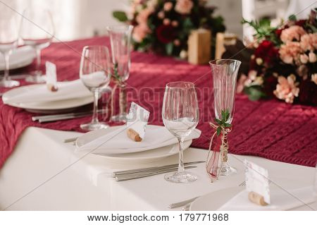 Wedding table decoration with the red and pink flowers on the red cloth