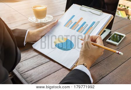 Business woman analyzing graph document with laptop and cell phone.