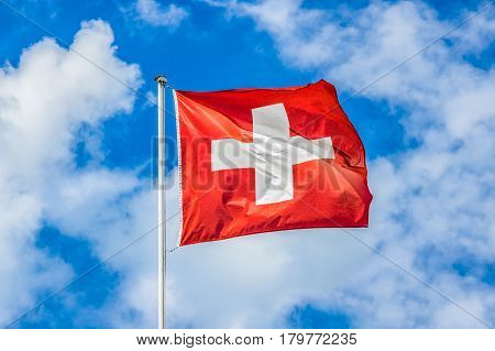 Classic view of the national flag of Switzerland waving in the wind against blue sky and clouds on a sunny day in summer on the First of August the national holiday of the Swiss Confederation