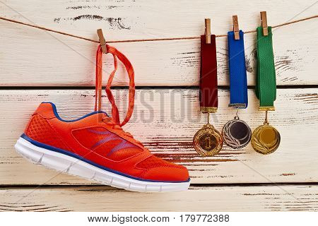 Sneaker and medals on clothesline. Sports competition and success.