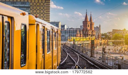 Panoramic view of Berliner U-Bahn with Oberbaum Bridge in the background in golden evening light at sunset with retro vintage Instagram style hipster filter effect Berlin Friedrichshain-Kreuzberg