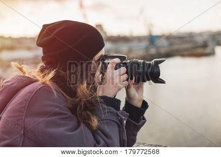 Female photographer taking photos of evening city