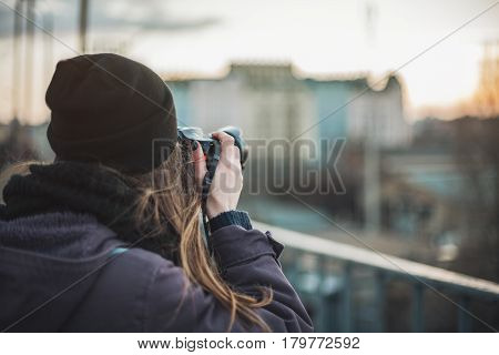 Female photographer taking photos of evening city