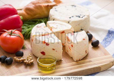 Variety of home made cheese and paprica and herbs olive oil olives and bread on a wooden board. brined curd white cheese with vegetables on the table