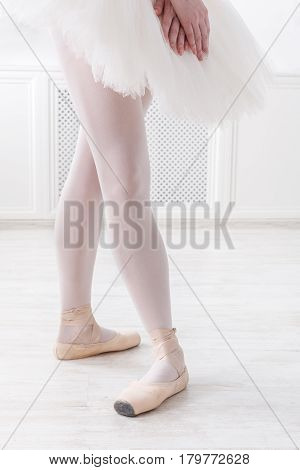Ballerina legs in fourth position on pointe, ballet dancer closeup background, vertical image