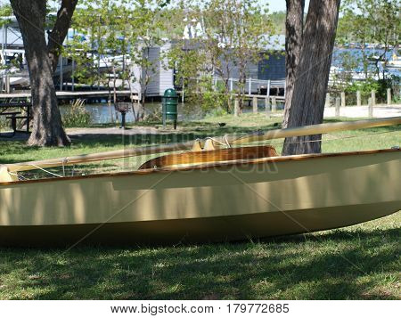 A sailboat is set out on the lawn before a regatta and advertised for sale.