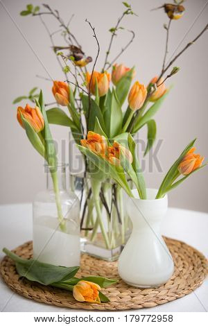 Fresh spring bunch of orange tulips and green leaves and small birds in nice cristal glass vases on the straw board and table with a tablecloth.