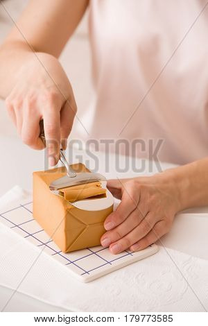 Closeup of woman's hands cutting traditional scandinavian organic brown cheese with cheese knife on kitchen table. Healthy Breakfast or snack. Healthy food and eating.