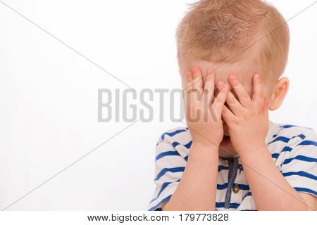 Portrait of a small toddler blond boy in a striped shirt hiding himself with hands. Child crying. Emotions.