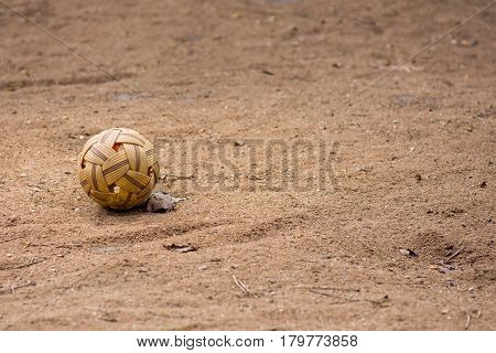 Sepak takraw kick volleyball ball alone on a dry dirt court.