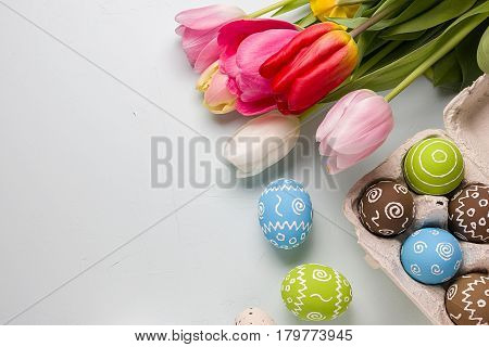 Painted easter eggs and bouquet of spring tulips closeup on a light blue background with space for congratulation
