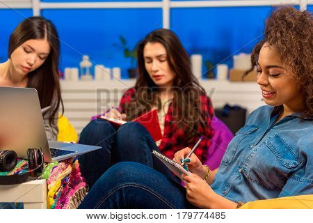 Focus on outgoing woman writing in notebook. She leaning on chair in wide room. Her friends sitting on background