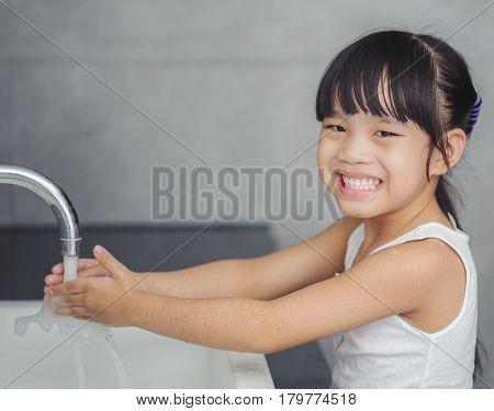 Cute little asian girl washing in bath