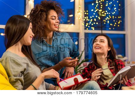 three women expressing happiness while discussing notes of friend. Deliberation concept