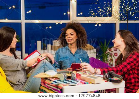 three women expressing pleasure while chatting in room. Conversation concept