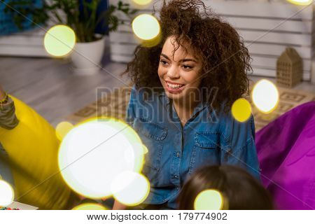 Portrait of smiling african female looking away. She dreaming while sitting in apartment