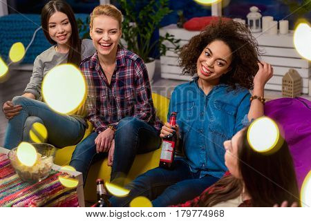 Outgoing female friends drinking beer while sitting on soft chairs around table. They making conversation. Friendship concept