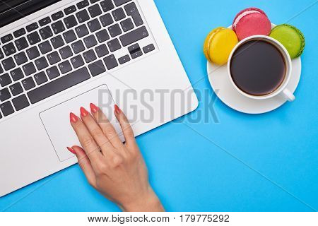High angle of skinny hand pressing a touchpad on laptop computer. Coffee and macaroons is placed next to the computer