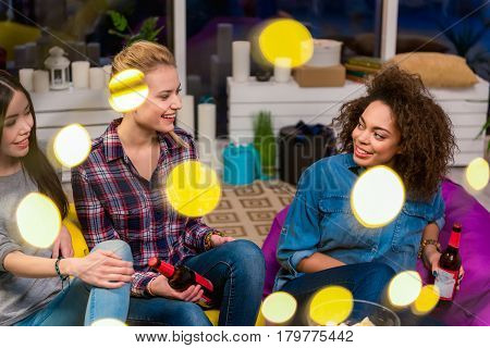 Cheerful asian, caucasian and african women chatting during party in apartment. They drinking beer