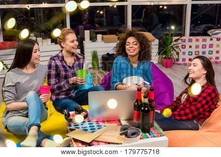Party in full swing. Cheerful african, asian and caucasian girls tasting beverage while sitting around table. They speaking with each other. Happy cocept
