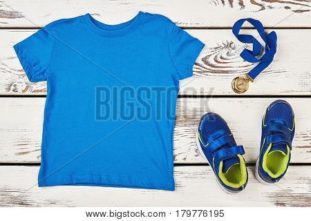 T-shirt, sneakers and medal. Distinction of sport achievements.