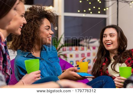 portrait of cheerful woman chatting with outgoing comrades during party. They drinking beverage. Conversation concept