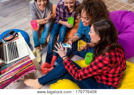 Top view of giggly female friends watching at mobile while sitting on soft chairs. Internet concept