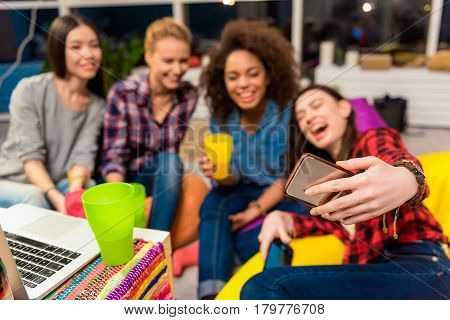 Focus on hand with cellphone. Cheerful women making cooperative selfie with happy friends